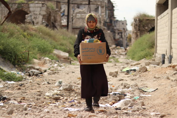 Girl holding a WFP box filled with items.